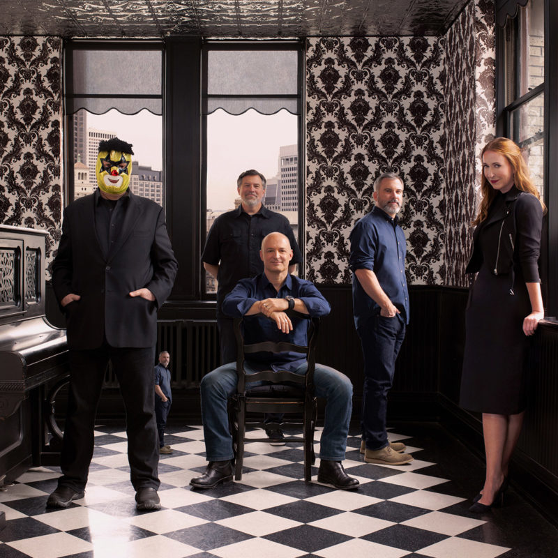 The partners of Duncan Channon; Robert Duncan, Parker Channon, Michael Lemme, Andy Berkenfield and Amy Coteleer are all polished in black posing sleekly for the camera. They are in a room with vintage designed wallpaper that is black in white. Robert Duncan is wearing his signature luchador mask.