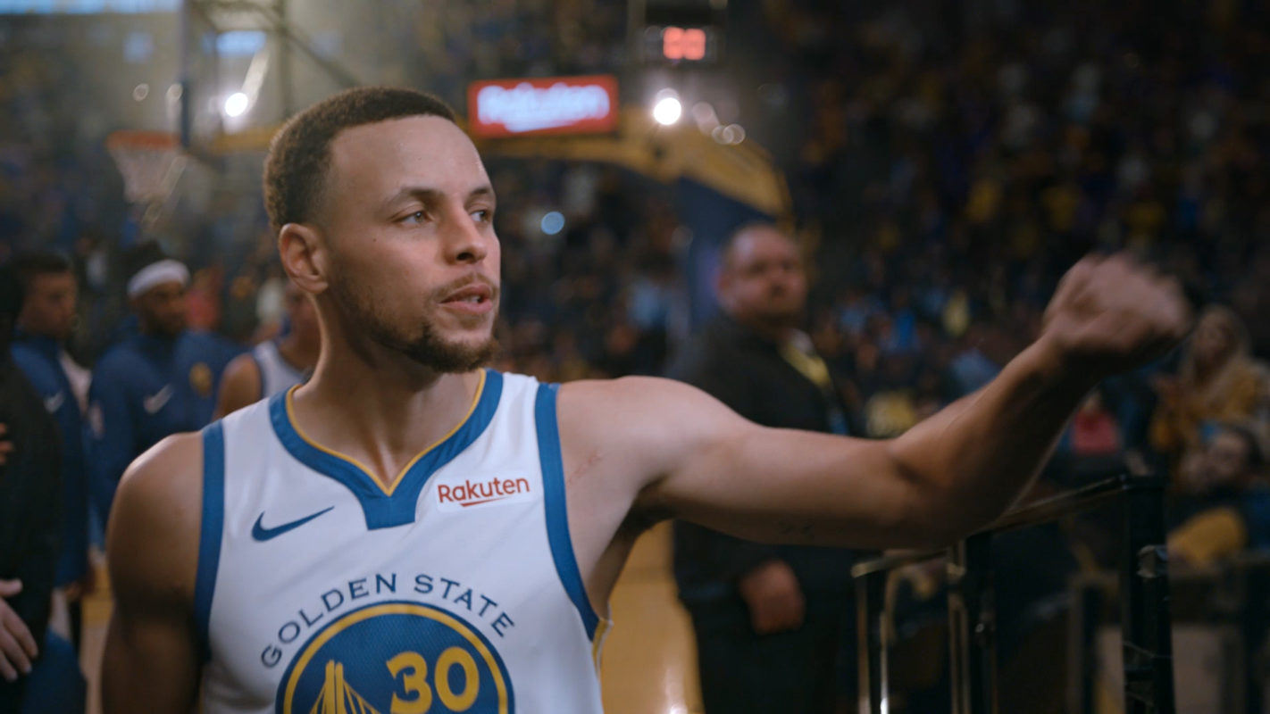 The one and only Steph Curry dats'up a fan as he walks off the court. He's in his classic white warriors uniform and it appears he is breaking for halftime during a busy game. In the background you can spot other players, fans and staff members.