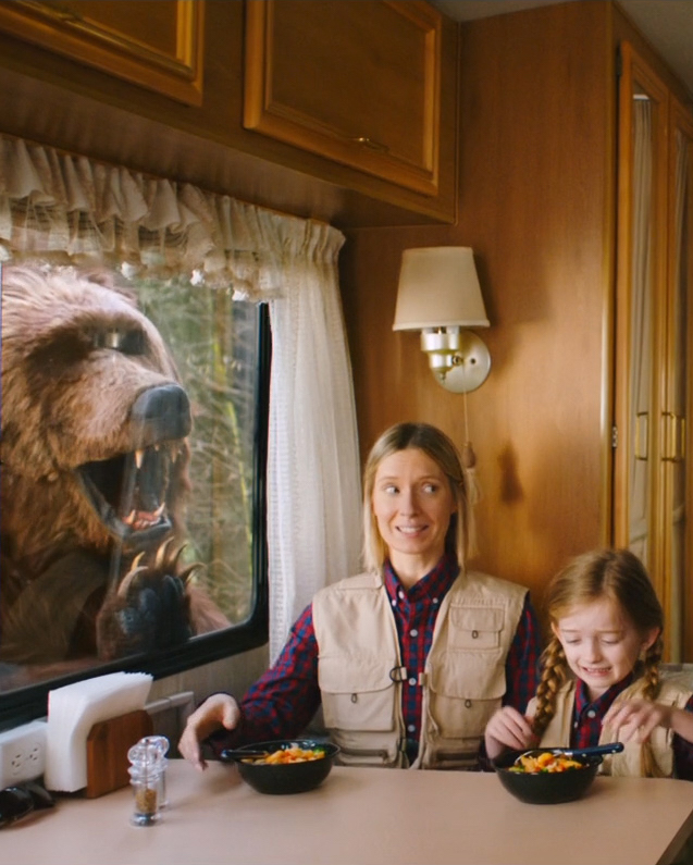 A mother and daughter are sitting at a booth inside a classic looking camper van. They are wearing matching red checkered flannels and a tan vest. They each have the same Innovasian meal in front of them. In the window of the camper is a giant bear that appears to want in on their tasty meal. The mother is giving her daughter the side eye as if the bear doesn't exist.