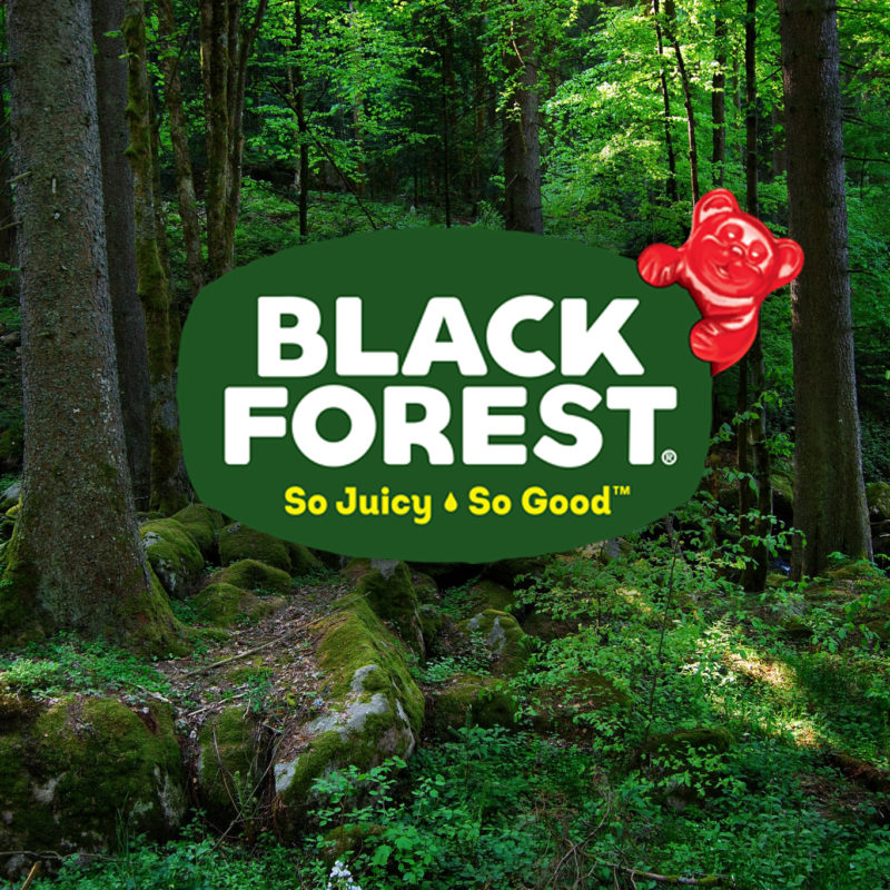 Black Forest, so juicy, so good. The Black Forest logo appears with a red gummy bear hanging over the top. In the background is a lush green forest. Sunlight peaks through and shines on a patch of green plants.