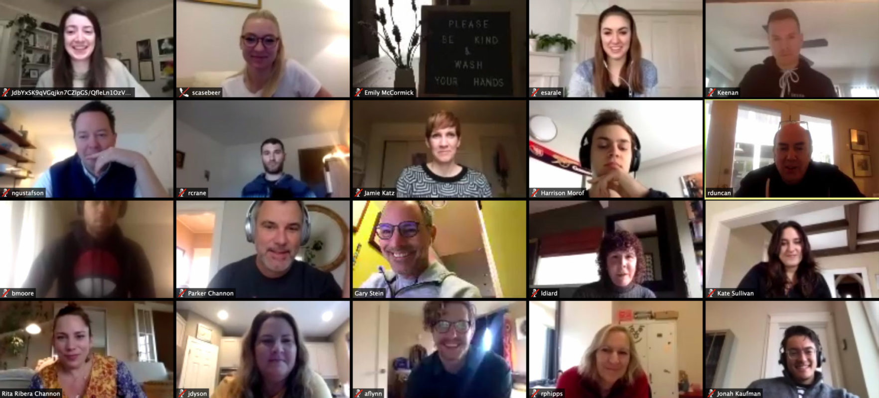 Grid image of 20 US employees on video conference call together. They are diverse in their age and their genders. They all appear smiling and some chatting like they are familiar with each other and enjoy working together.