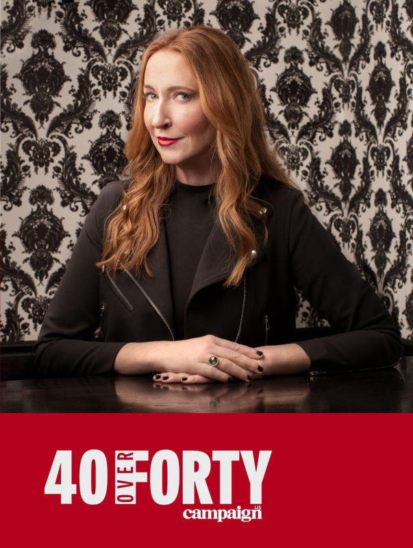 "Amy Cotteleer poses for a headshot in front of black and white vintage wallpaper. Below her image in red with white text reads ""40 over 40 campaign"""
