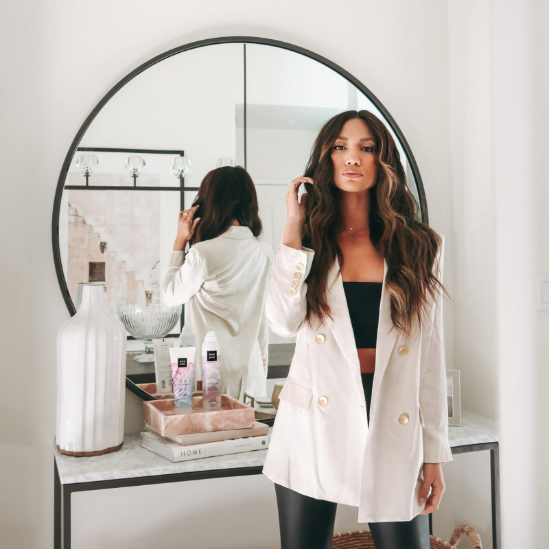 Female presenting influencer posing for the camera in a sleek white blazer and leather black pants. She is confident and raises her hand to perfect her long brown hair that is styled in a middle part and she's wearing make-up that accentuates her strong features. She's in front of a mirror with a table with SGX NYC products.