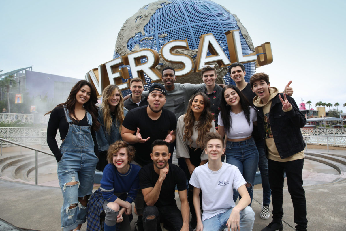 A diverse group of young adults pose and smile in front of the universal studios lifesize logo in Orlando, Florida.