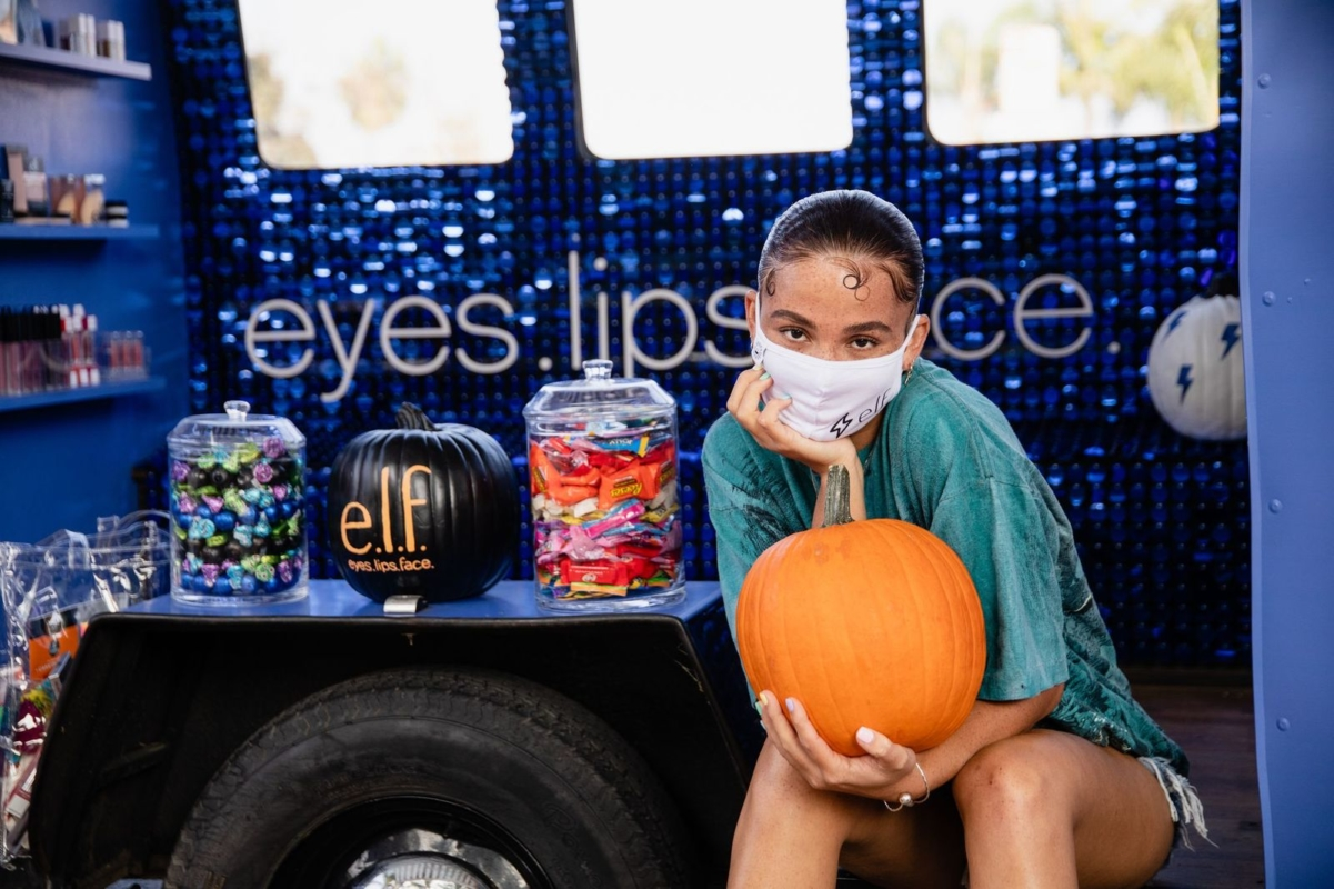female presenting person wearing teal shirt and white e.l.f. branded face mask, holding orange pumpkin while sitting inside pop-up vehicle with purple sparkly wall behind her with the words