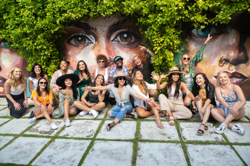 Group photo of 16 people sitting in front of a mural of faces, painted underneath plants that resemble hair. The people in the photo are all smiling and having a great time.