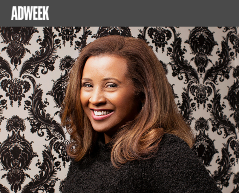 Portrait of DC employee Kumi Croom. She is smiling warmly and wearing a dark sweater, posting against black and white Jacquard pattern wallpaper. The ADWEEK logo appears in the top left corner.
