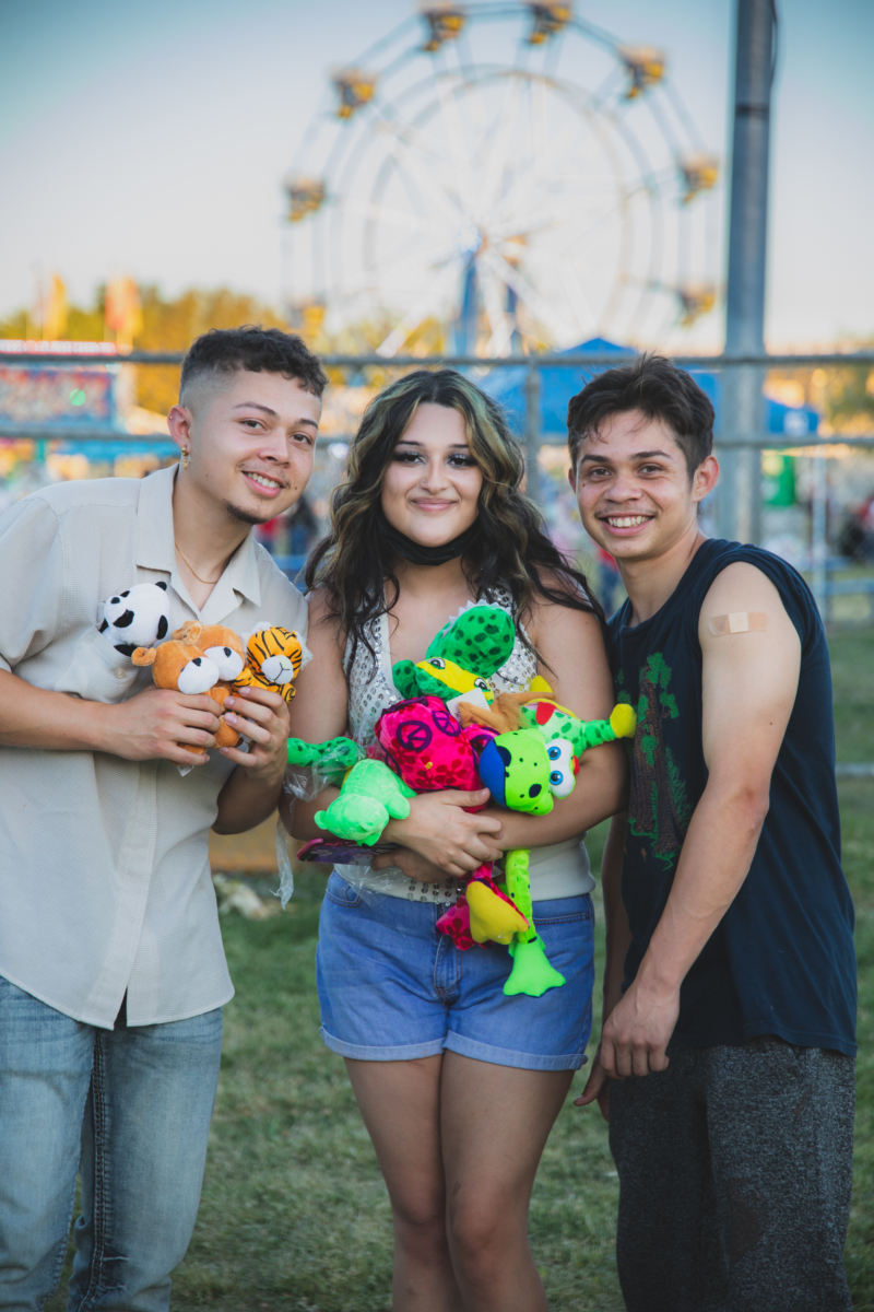 Three people stand together smiling at a carnival. One proudly shows the bandaid on their recently vaccinated arm and the other two hold colorful prizes they won at the carnival.